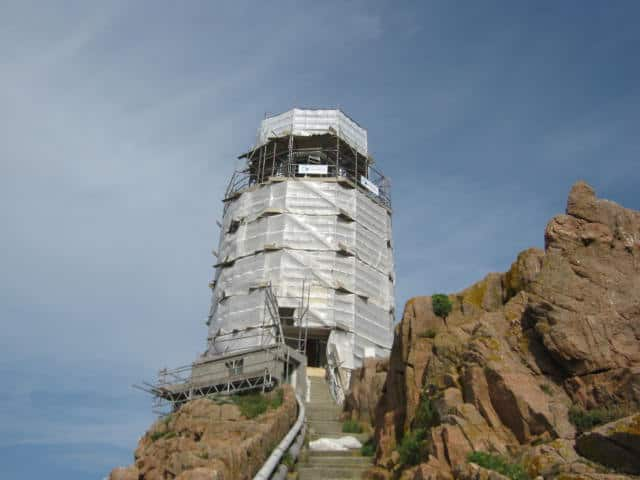 encapsulated lighthouse on top of stairs with nearby rocks