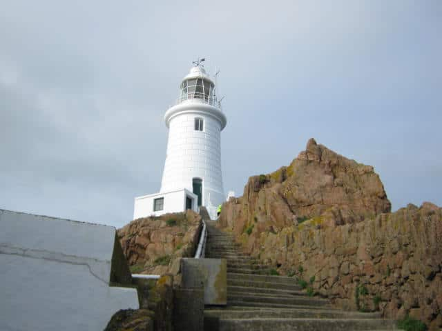 white lighthouse on top of stairs with nearby rocks