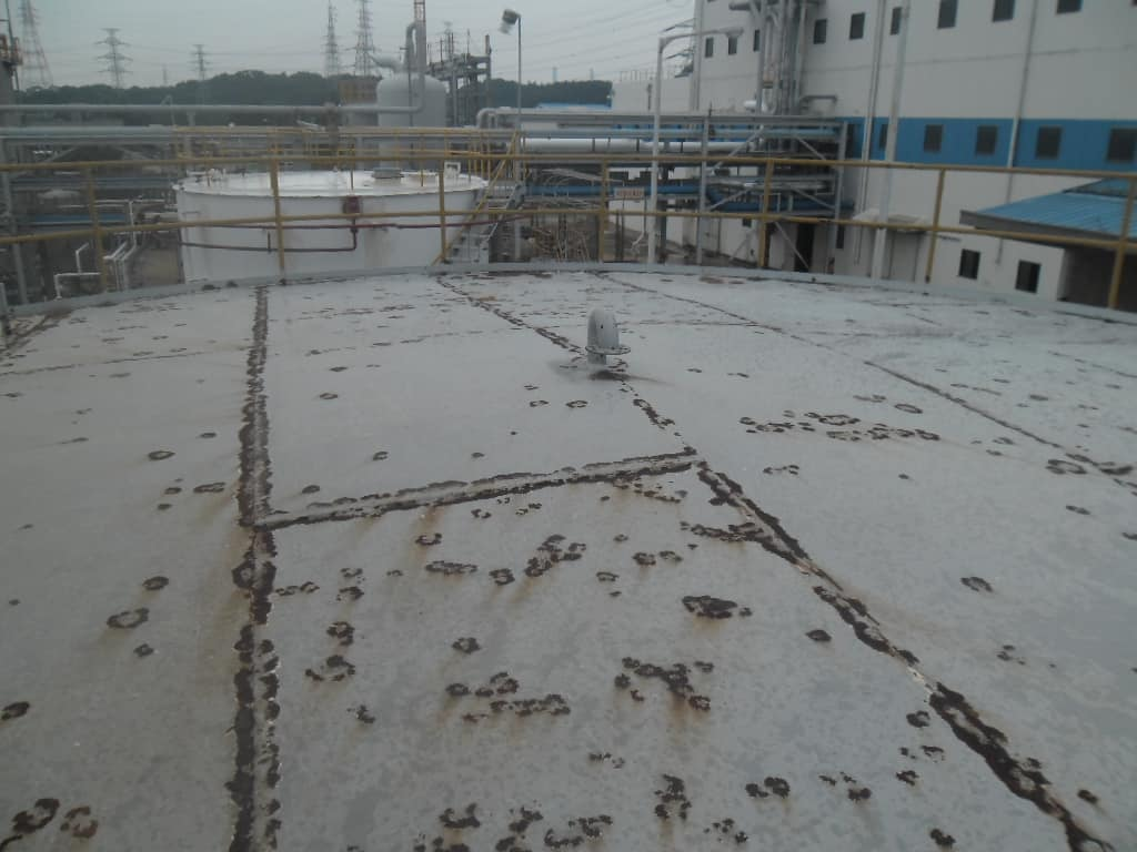 unpainted crude oil tank roof with rusted yellow railing