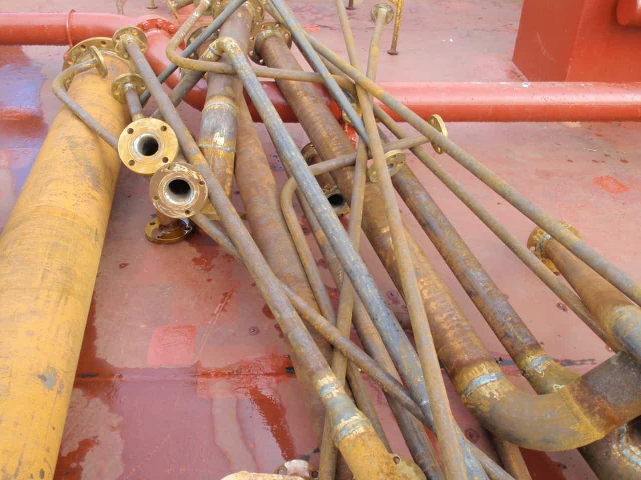 bundle of heavily rusted pipes on red floor