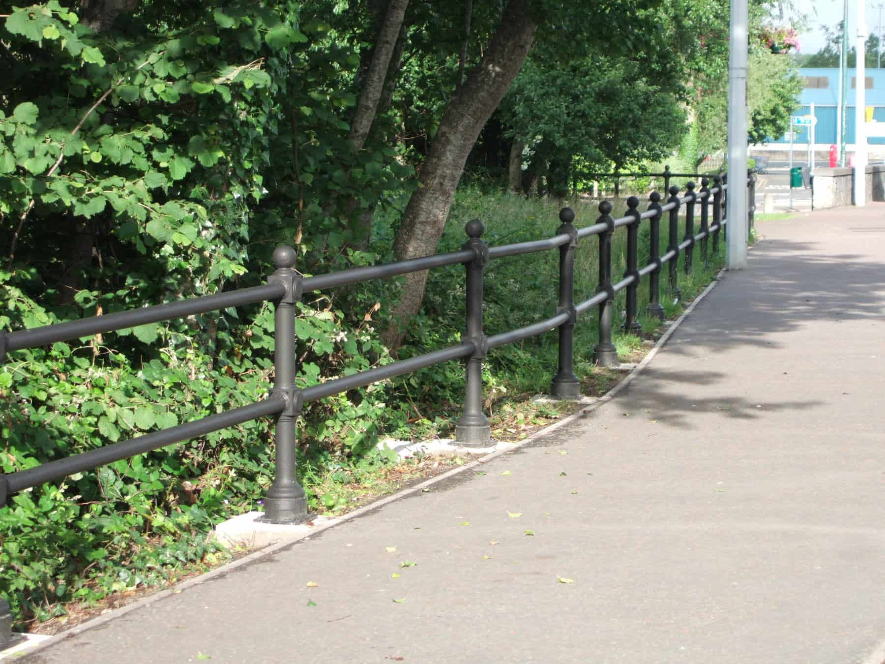 black public railings next to pathway and trees