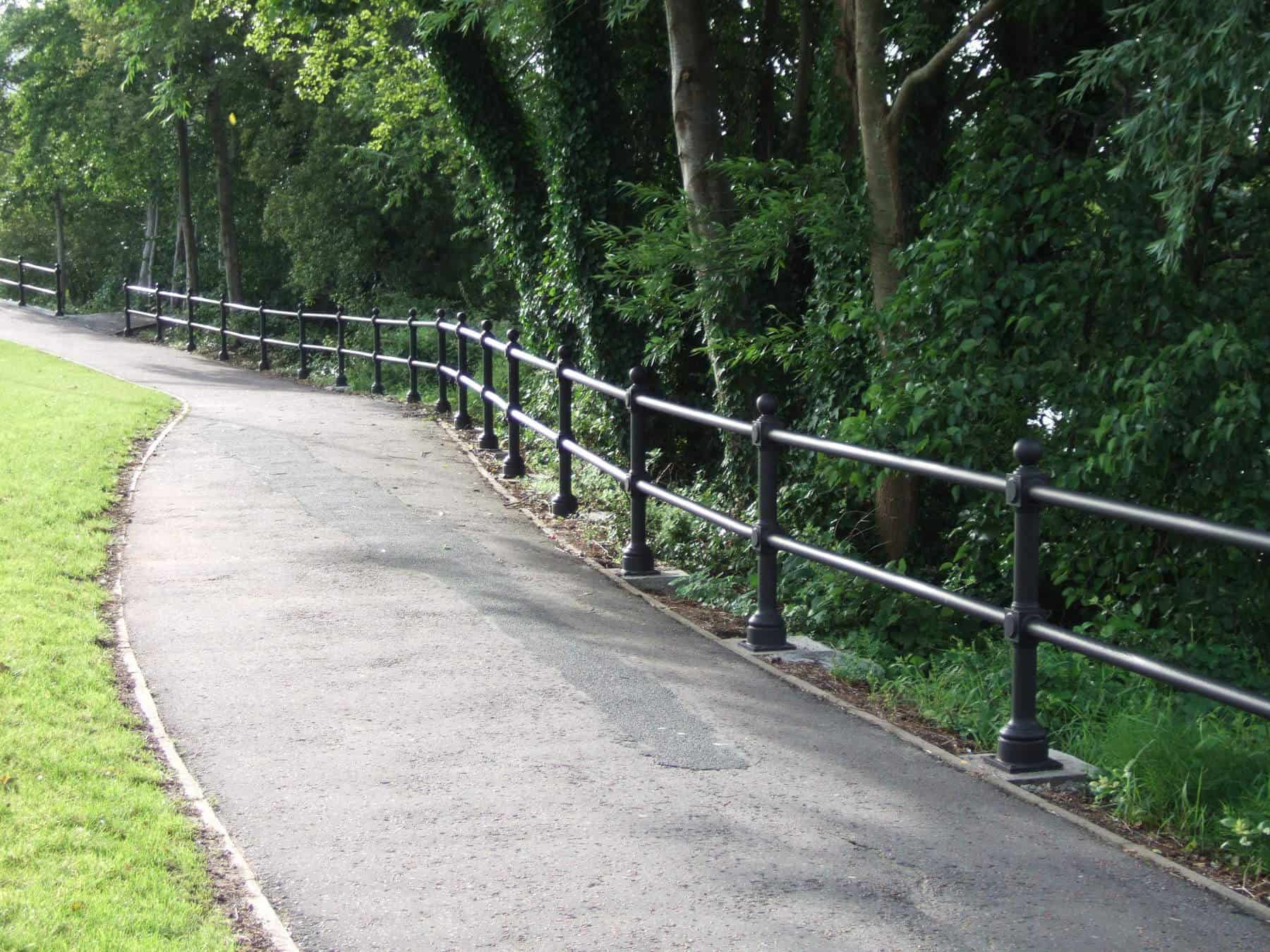 black public railings next to pathway and grass