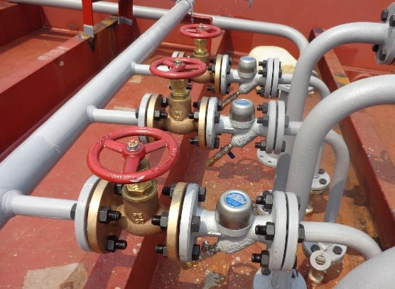 external painted steam pipes on red decking