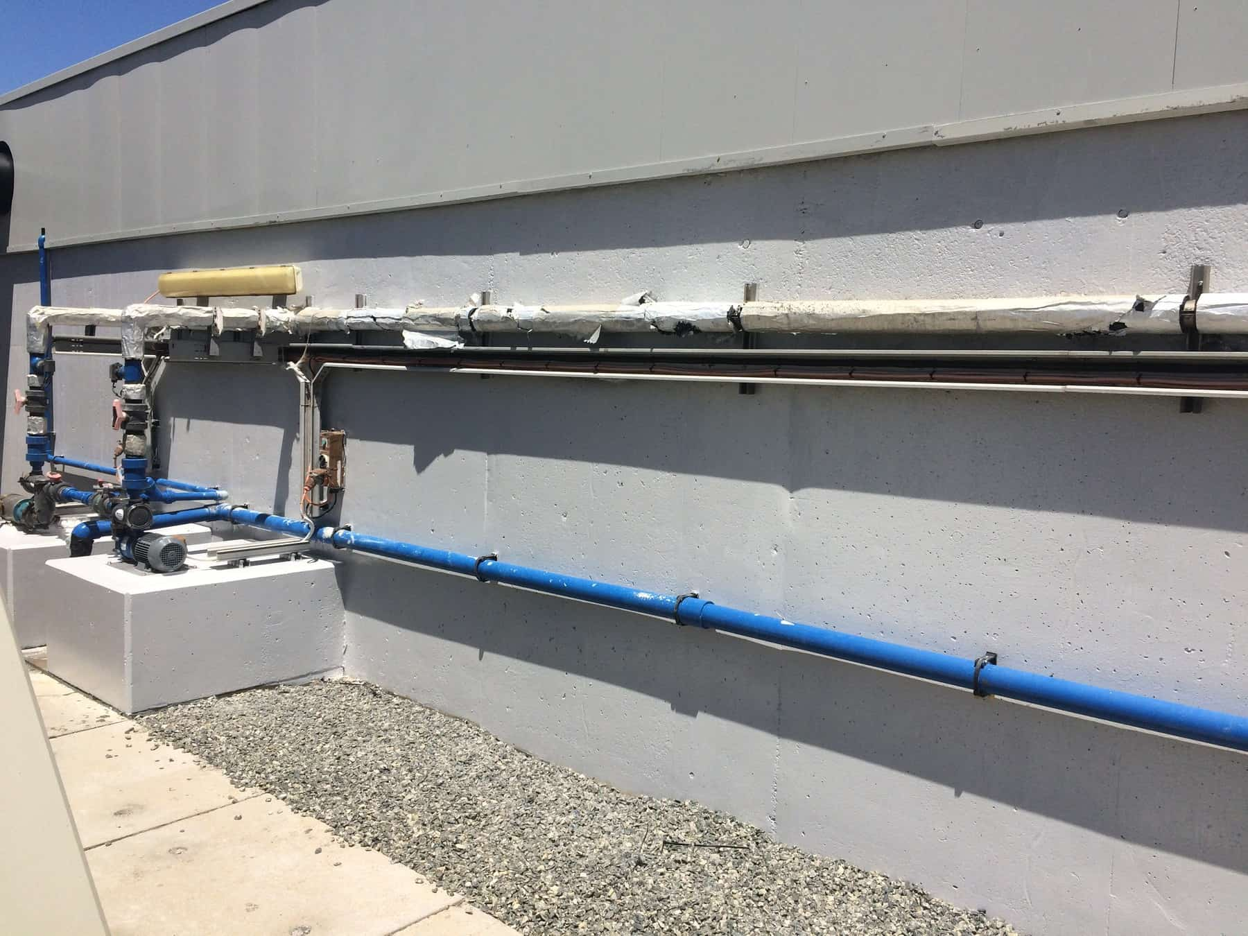 external concrete wall with horizontal pipes above gravel