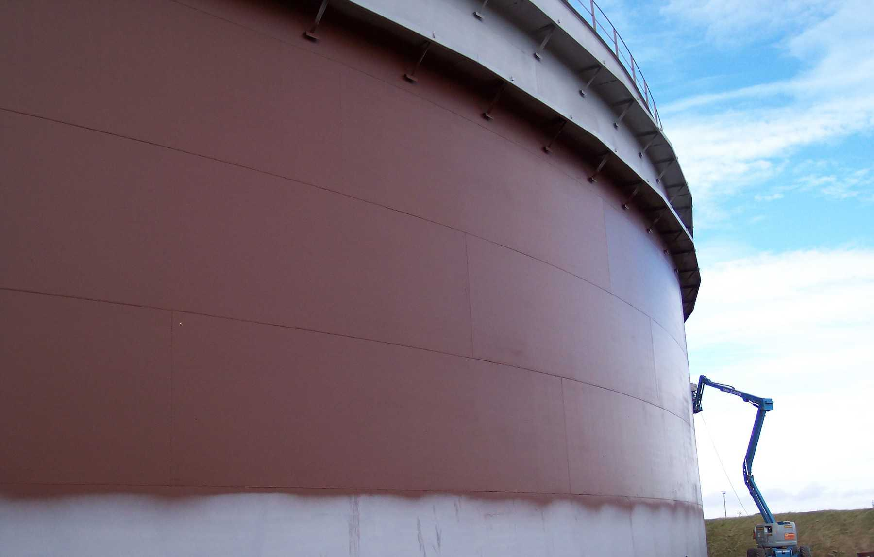 external oil tank painted in dark red with cherry picker