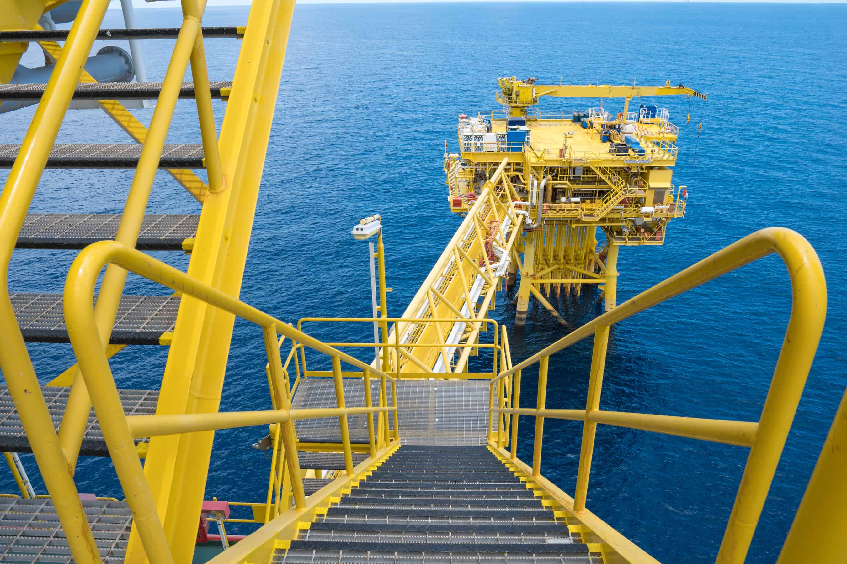 offshore platform painted yellow with metal steps
