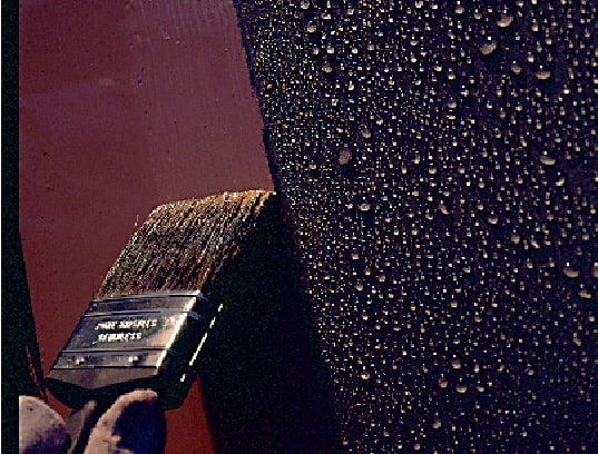 brush application of maroon paint to sweating substrate