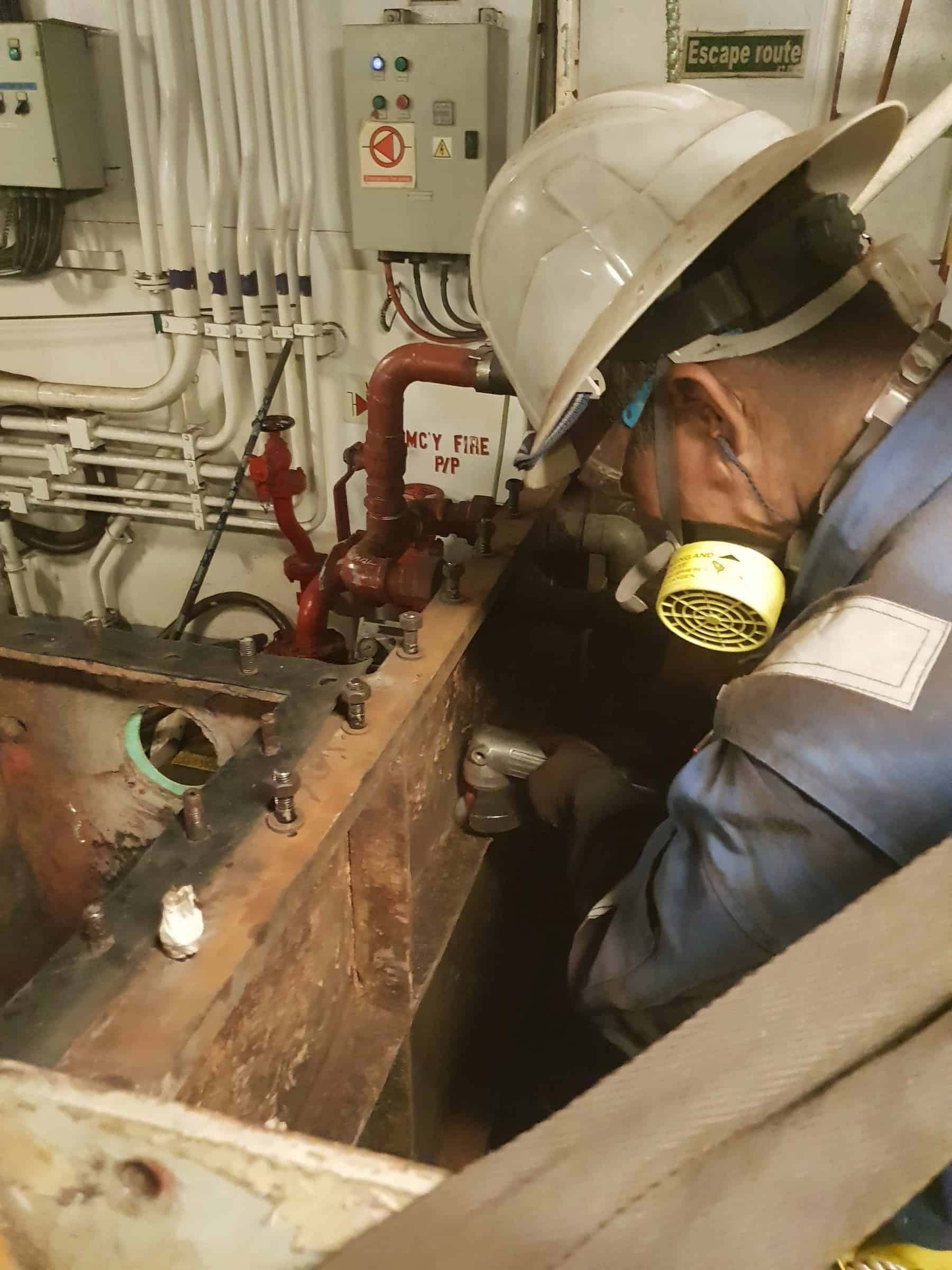 Man preparing rusted sewage tank steel with power tool