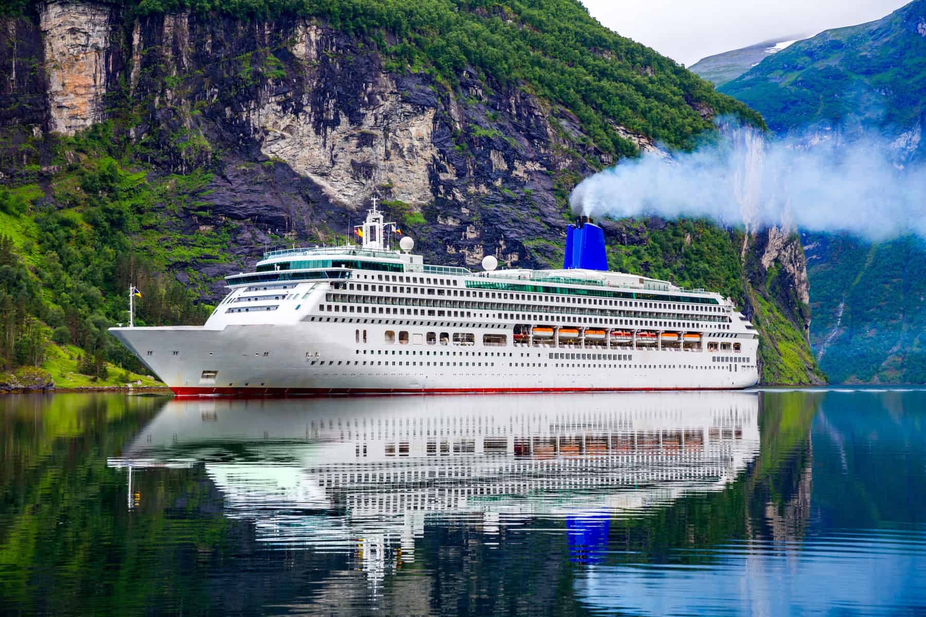 large cruise ship in sea with colourful cliff background