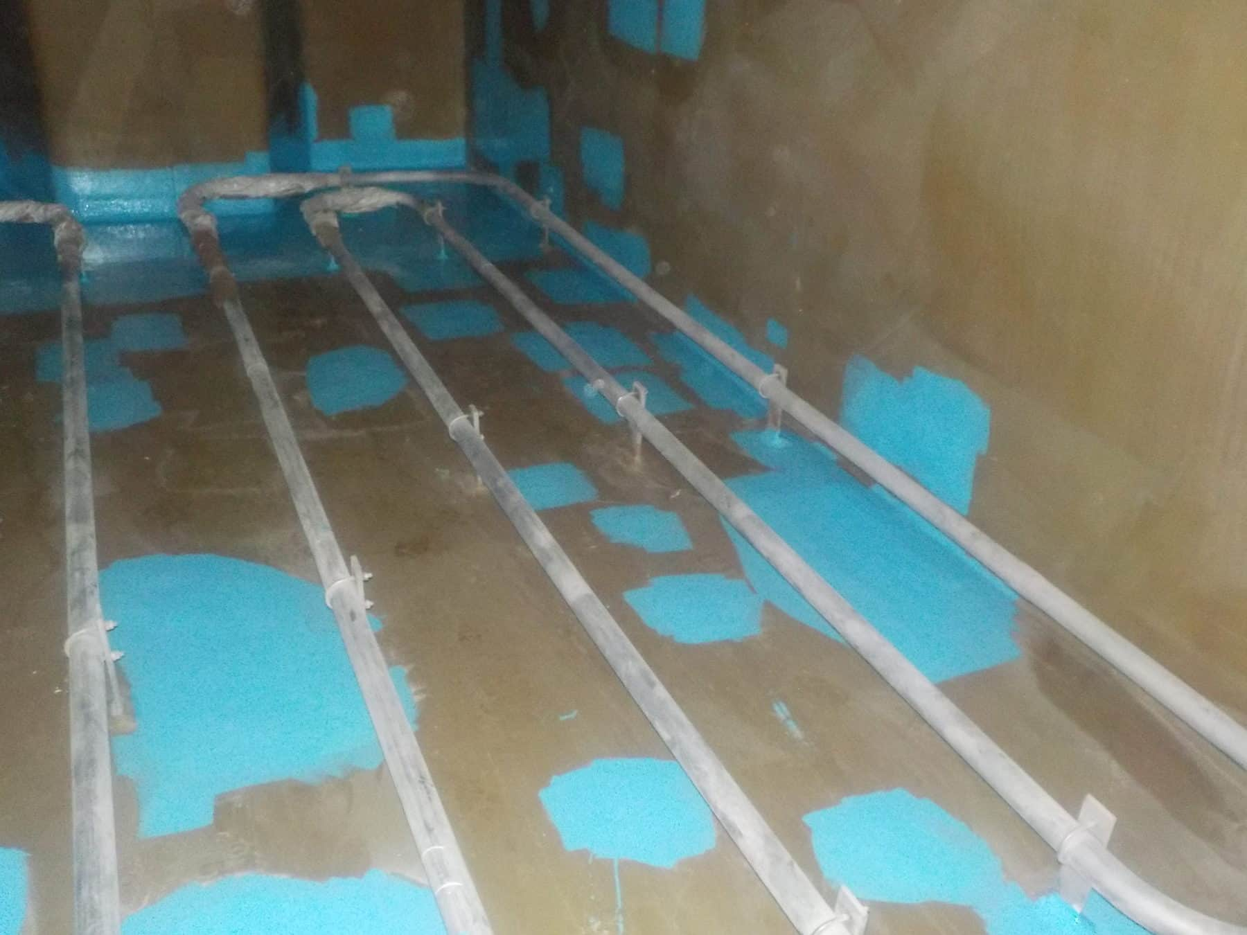 tank internals with blue paint spots and steel piles
