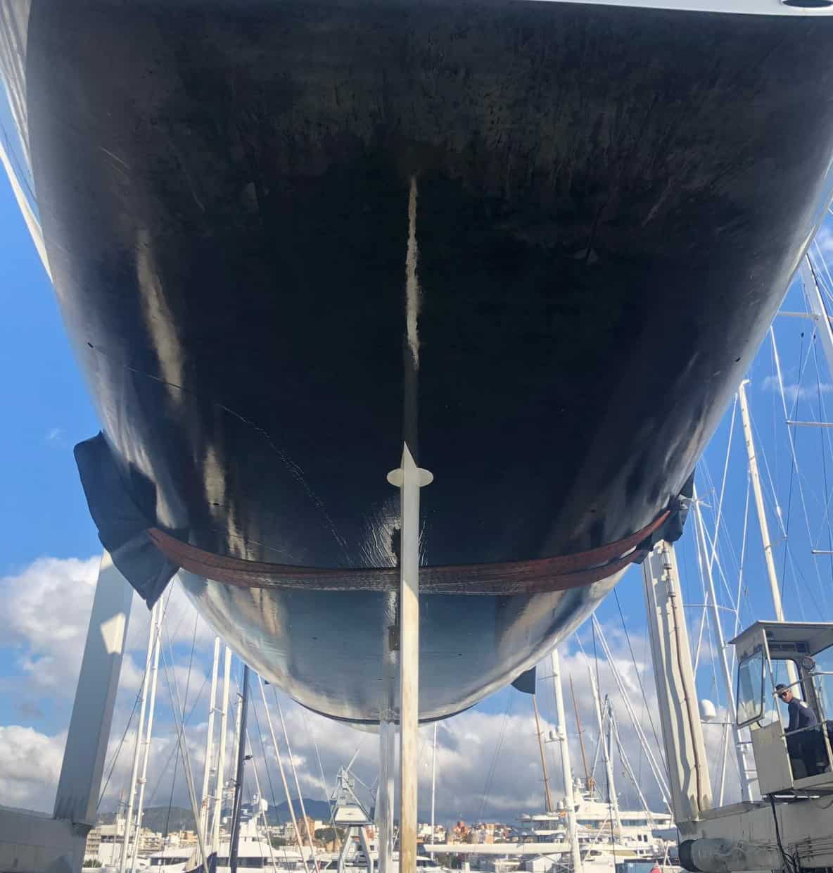 close up of black yacht hull exterior in dock