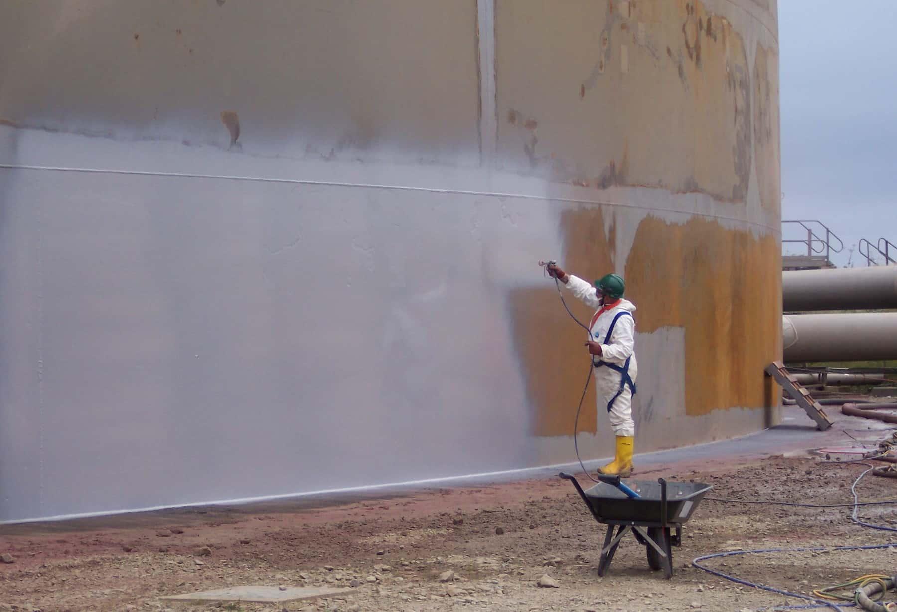 sprayer applying grey coating to tank internal