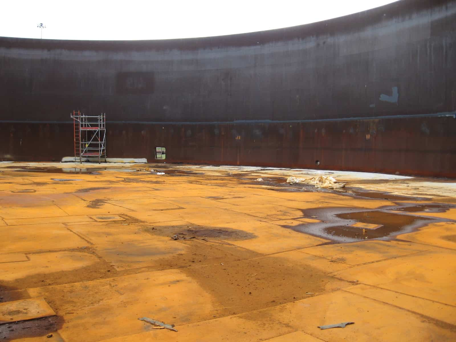 rusted floating tank roof with small staging